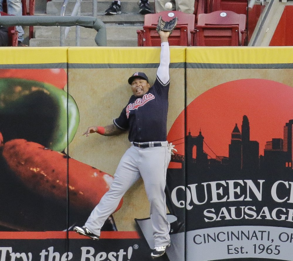 Cleveland center fielder Marlon Byrd hits the wall as he just misses a solo homer by the Reds' Jay Bruce in the Indians' 8-7 win Wednesday at Cincinnati.