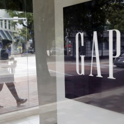 A pedestrian walks past a Gap store in Miami. Gap said Thursday that it plans to close 75 Old Navy and Banana Republic stores outside North America.