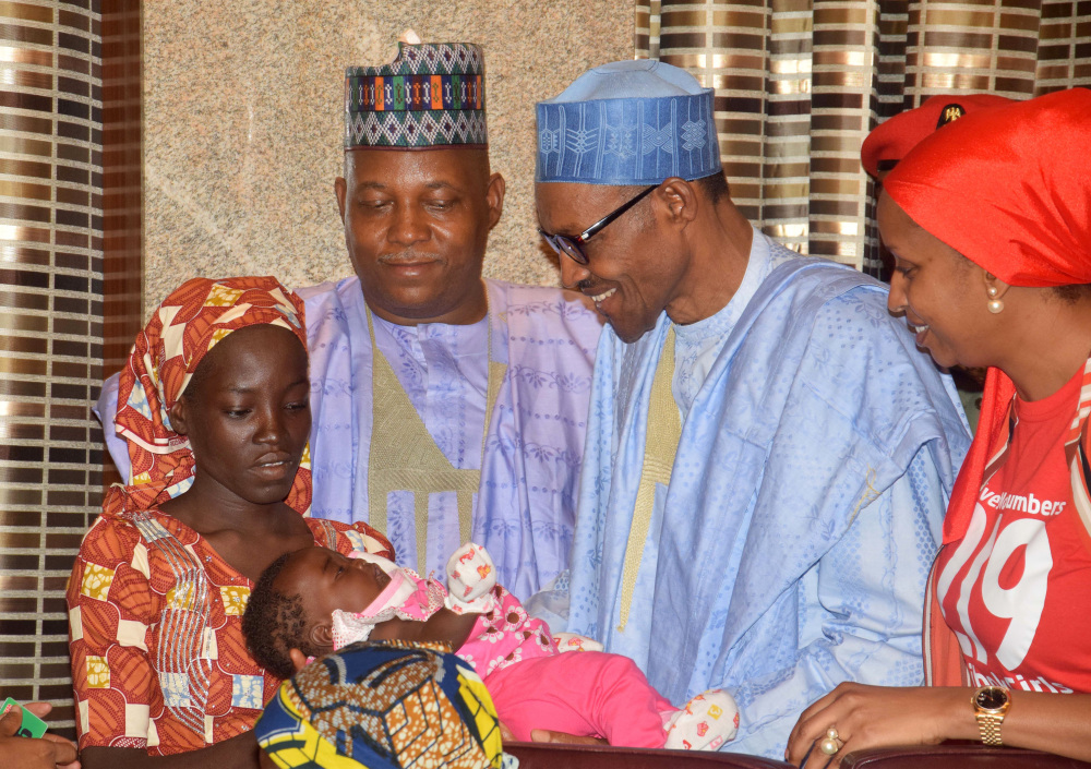 Nigeria's President Muhammadu Buhari, second from right, receives Amina Ali Nkeki, left, the rescued Chibok school girl, at the Presidential palace in Abuja, Nigeria, on Thursday.