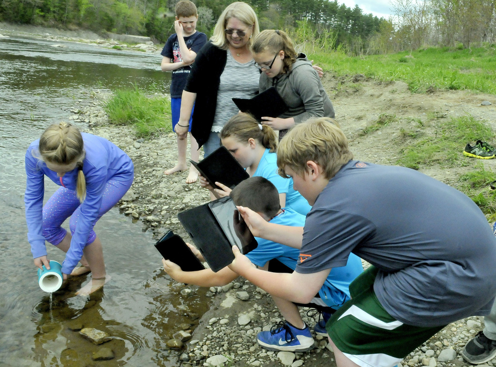 Teacher Patricia Dunphy, center, watches as students photograph Peyton Estes releasing salmon fry into Sandy River in Norridgewock on Thursday.