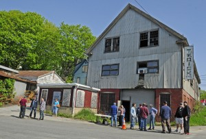 An auction Friday draws bidders and onlookers at the former T.W. Dick Co. steel fabricating facility in Gardiner. The vertical sign on the building's corner drew the highest bid at $1,500.