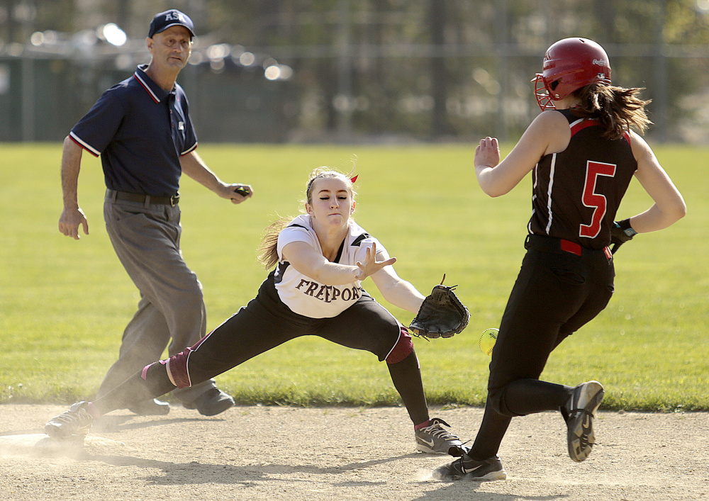 Freeport second baseman Kasey Erlebach attempts to handle a throw as Olivia Durfee of Wells arrives safely. Durfee had three of the 15 hits for Wells.