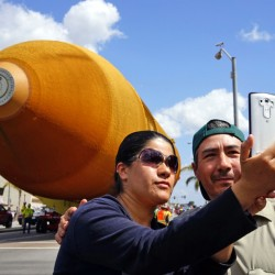 A couple takes a selfie as a massive space shuttle external fuel tank, the last one in existence, moves past on a street in Inglewood, Calif., en route from Marina Del Rey to the California Science Center in downtown Los Angeles on Saturday.