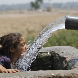 Water from an irrigation tube provides relief to a girl on the outskirts of Jammu, India, on Saturday.