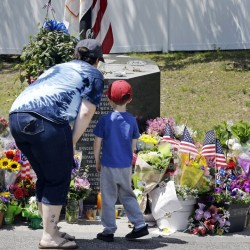 Danielle Dowd and her son Lucas pause before a memorial set up for slain Auburn police Officer Ronald Tarentino outside the police station in Auburn, Mass., on Monday. The man suspected of killing Tarentino during a weekend traffic stop had a lengthy criminal record.