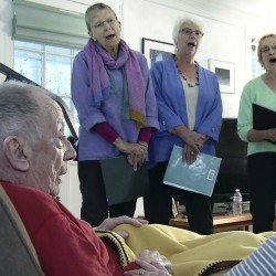 """In a still image taken from video, members of the choir JourneySongs sing for Norman Doelling at his home in Newton, Mass. """"It was very charming. I have a great deal of appreciation. It was very nice of them to come and sing to an old man,"""" said Doelling, 85, who recently had a stroke."""