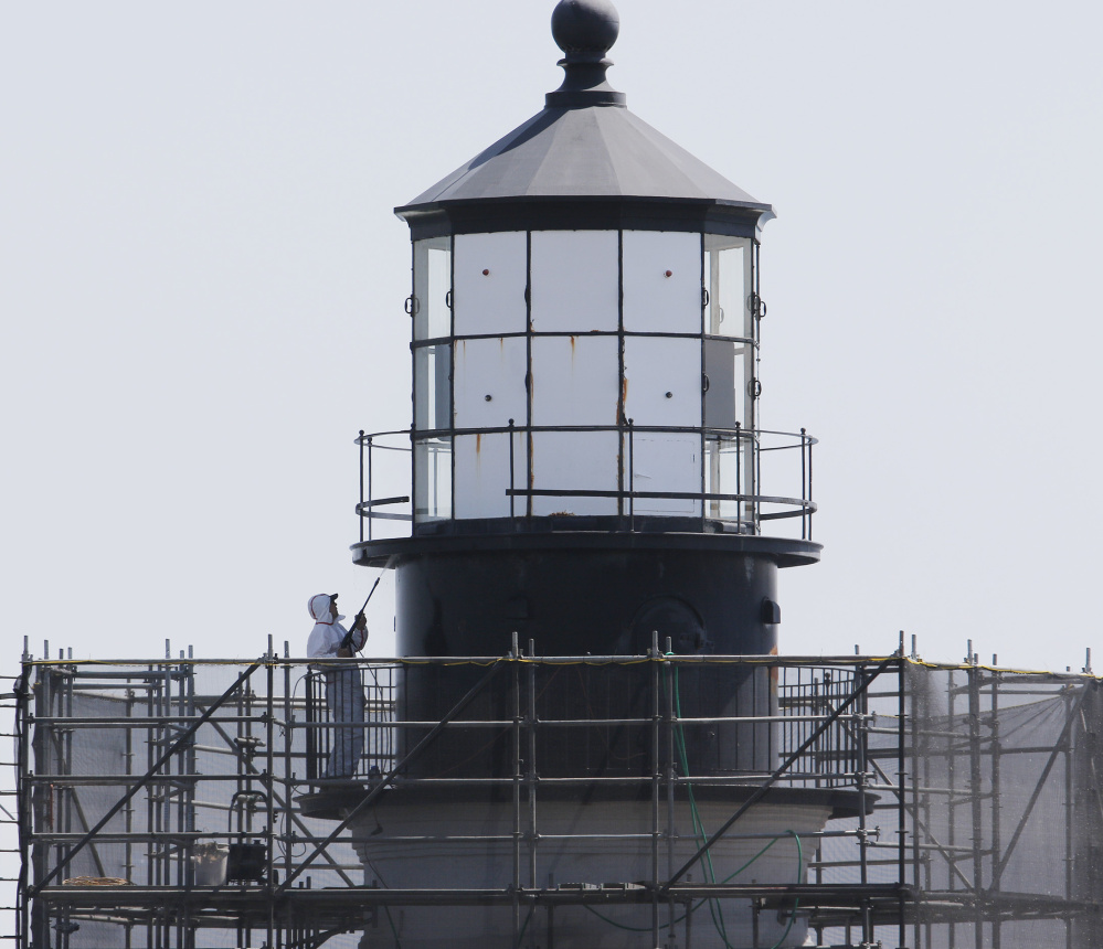A worker pressure-washes a section near the top of the lighthouse, which is due for masonry repairs and painting.