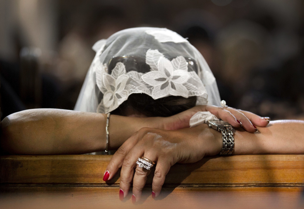 A Coptic Christian woman grieves during prayers for the departed Sunday, remembering the victims of Thursday's crash of EgyptAir flight 804, at Al-Boutrossiya Church, the main Coptic Cathedral complex, in Cairo, Egypt.
