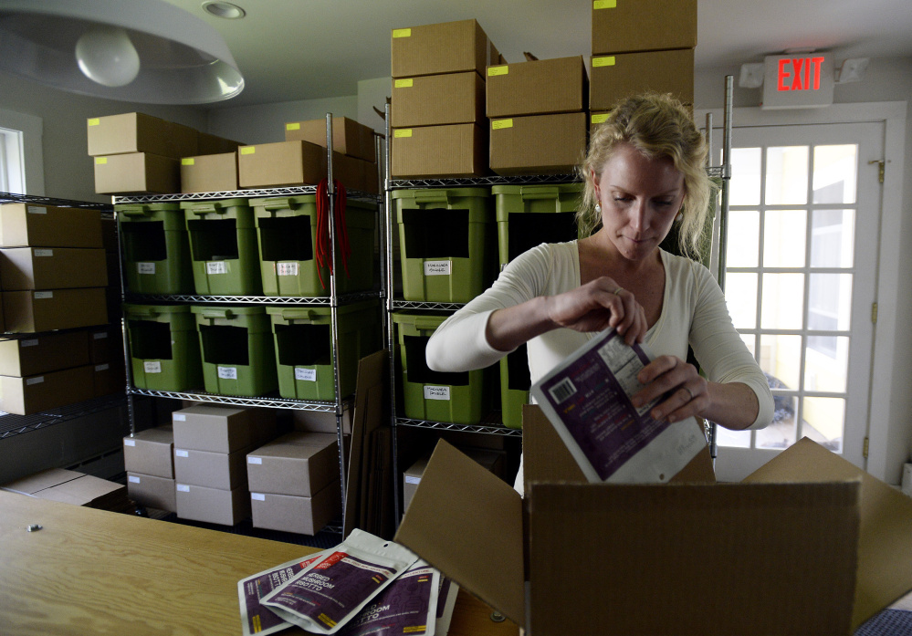 Kate Newport prepares packages for shipping at Good To-Go in Kittery. The packages include Maine ingredients in the packaged meals.