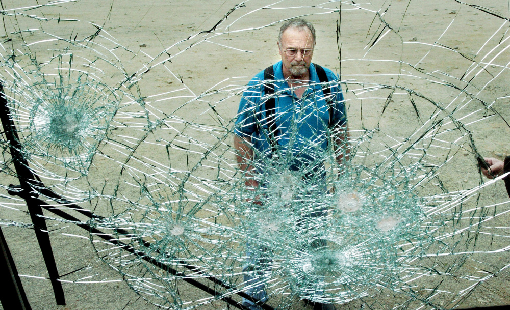 School Administrative District 54 Transportation Director Gary Savage surveys a smashed windshield in a district school bus Tuesday. Several spare buses parked near the  garage on Maple Street in Skowhegan had windows broken.