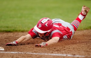 Alex Livingston sends the dirt flying Tuesday while sliding back to first base on a pickoff attempt during South Portland's 2-1 victory against Biddeford. The Red Riots have won eight of their past nine games.