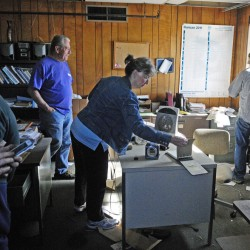 Carole Quackenbush, center, looks around the upstairs office during the preview for an informal auction last week at the former T.W. Dick facility in Gardiner. The facility will be cleaned up using federal funds.