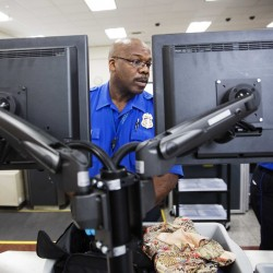 A TSA officer looks at a screen while checking a bag at a newly designed screening lane at Hartsfield-Jackson Atlanta International Airport Wednesday.