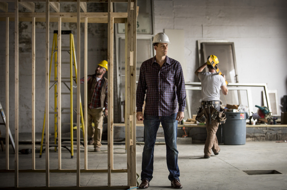 "Nik Caner-Medley monitors construction at a co-working, meeting and event space called Cloudport that is due to open in July at 59 Federal St. in Portland. ""I want to be smart with my money and invest it in my community,"" he said."