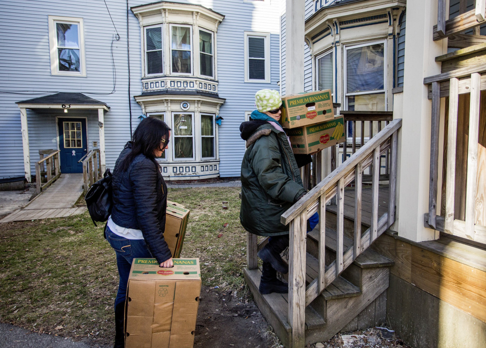 Chrissy Whitlock, left, helps Anna Teague move up to her apartment on Grant Street in February. Teague is one of many residents who have been evicted because of a building being sold and then renovated.