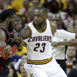 LeBron James of the Cavaliers looks to pass around Toronto's DeMarre Carroll in the first half Wednesday at Cleveland.