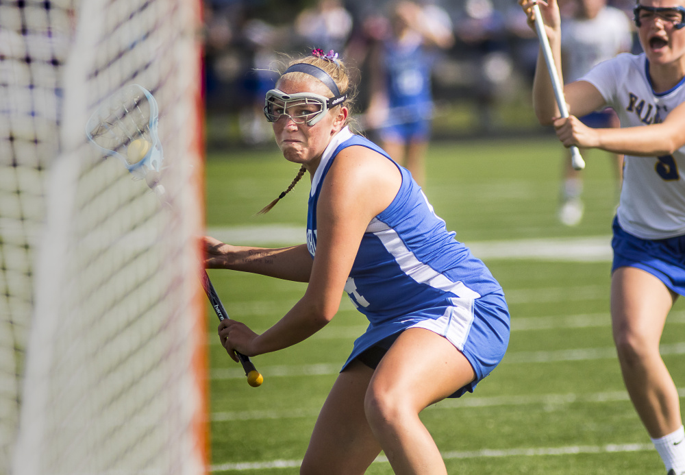 Carly Sandler of Kennebunk winds up for a goal Thursday after a free position against Falmouth. Kennebunk came away with  a 7-6 overtime victory in a game between undefeated girls'  lacrosse teams. Ben McCanna/Staff Photographer