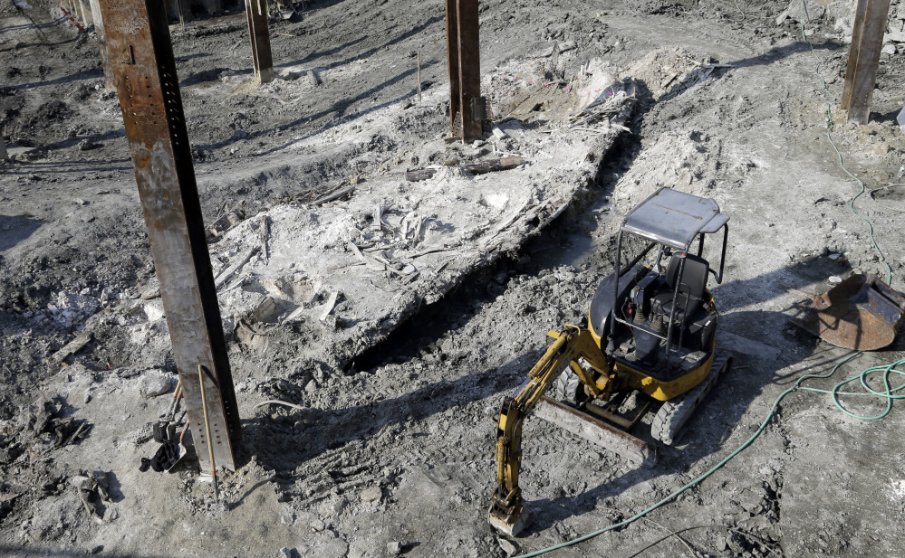 The outline of a shipwreck from the 1800s that was uncovered during construction in the Seaport District is seen to the left of a construction vehicle on Wednesday in Boston.