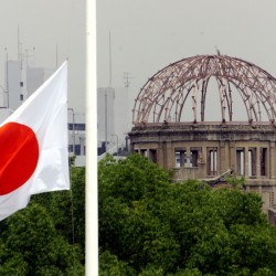 The Japanese national flag flutters at half-staff in the foreground of the atomic bomb dome at the Hiroshima Peace Memorial Park in western Japan.