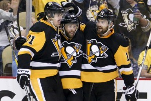 Bryan Rust of the Penguins, center is congratulated by Evgeni Malkin, left, and Ben Lovejoy after scoring his first goal Thursday night in Game 7 of the Eastern Conference finals against Tampa Bay.