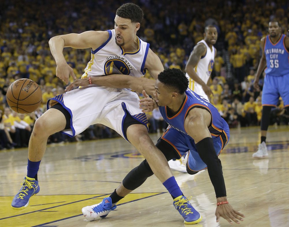 Warriors guard Klay Thompson, left, and Oklahoma City's Russell Westbrook reach for a loose ball in the first half of Game 5 of the Western Conference finals Thursday night in Oakland, Calif.