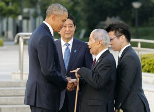 President Obama, left, shakes hands and chats with Sunao Tsuboi, second right, a survivor of the 1945 atomic bombing and chairman of the Hiroshima Prefectural Confederation of A-bomb Sufferers Organization, as Japanese Prime Minister Shinzo Abe watches them during his visit to Hiroshima Peace Memorial Park in Hiroshima, western Japan, Friday.