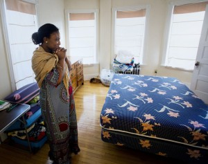 Bibiche Bekoka takes a moment for herself after receiving furniture from Furniture Friends, an organization that provides furniture to families in need across the Portland area. Bekoka, a mother of four from South Africa, has been sleeping on an air mattress with two of her children since moving to Portland.