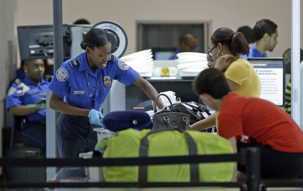 A Transportation Security Administration officer checks travelers luggage to be screened by an x-ray machine at a checkpoint at Fort Lauderdale-Hollywood International Airport, Friday, May 27, 2016, in Fort Lauderdale, Fla. Memorial Day weekend, the unofficial start of summer vacations for many and a busy travel period, serves as a crucial test for the TSA. (AP Photo/Alan Diaz)