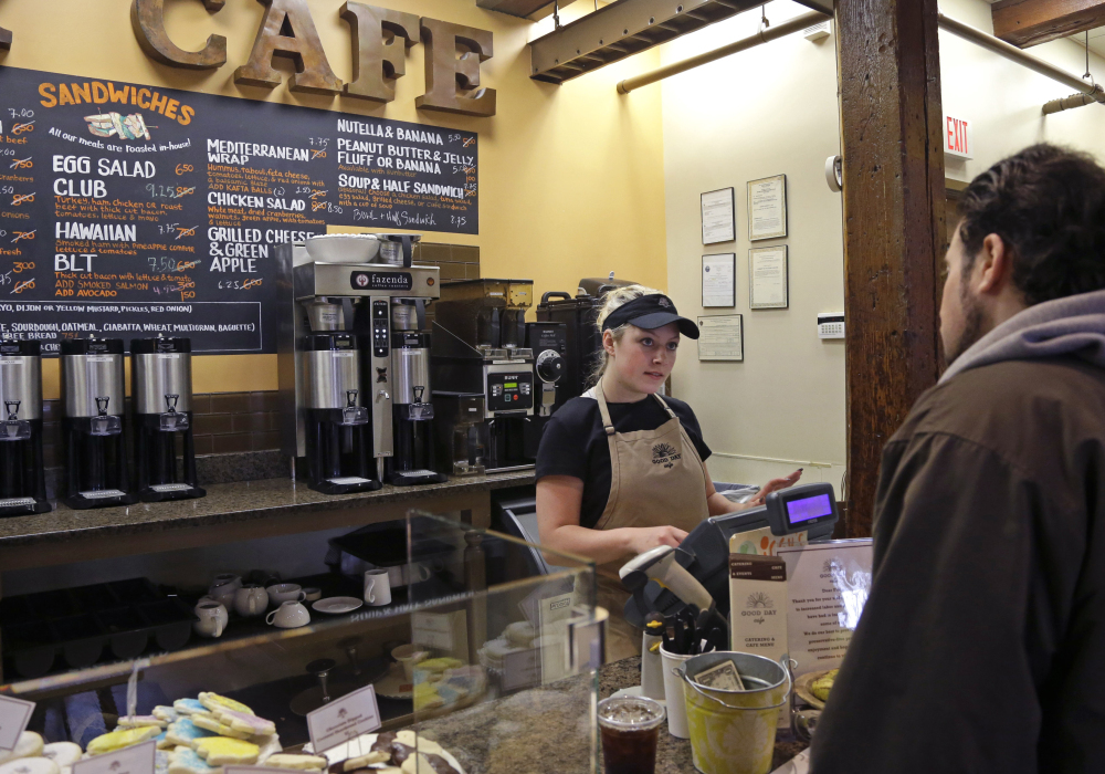 Kayla Mitchell serves a customer at Good Day Cafe in North Andover, Mass., on Friday. An initial assessment on U.S. growth has been revised upward.