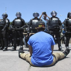 A woman sitting in the street faces riot police after a campaign rally for Republican presidential candidate Donald Trump in Fresno, Calif., on Friday. The crowd beat drums, chanted anti-Trump slogans and marched around the arena in downtown Fresno.