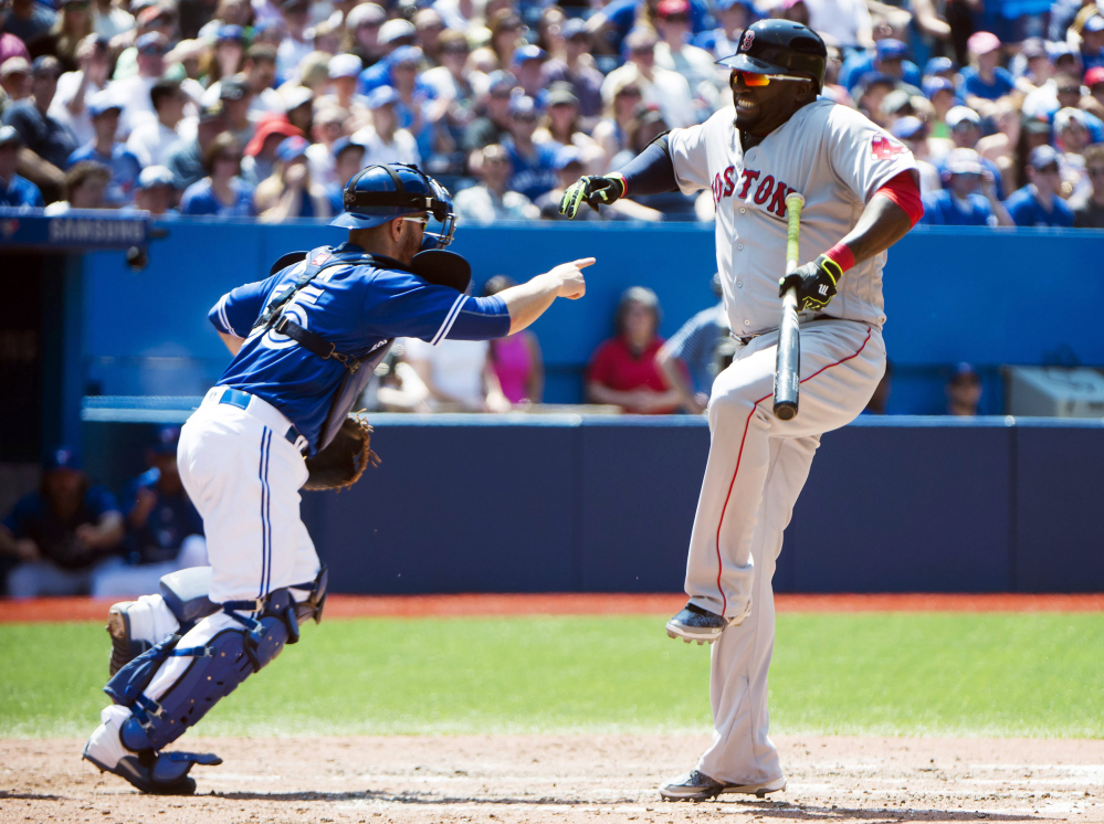 Boston Red Sox designated hitter David Ortiz reacts after apparently taking a foul ball to his leg as Toronto Blue Jays catcher Russell Martin (55) looks on during the fifth inning on Saturday.