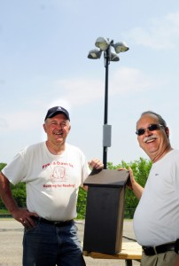 Augusta City Councilor Pat Paradis, left, poses with Ray Fecteau and a bat house at the Mill Park pétanque courts in Augusta. Fecteau said he hopes the bats will devour bugs attracted to the lights at the court during evening play.