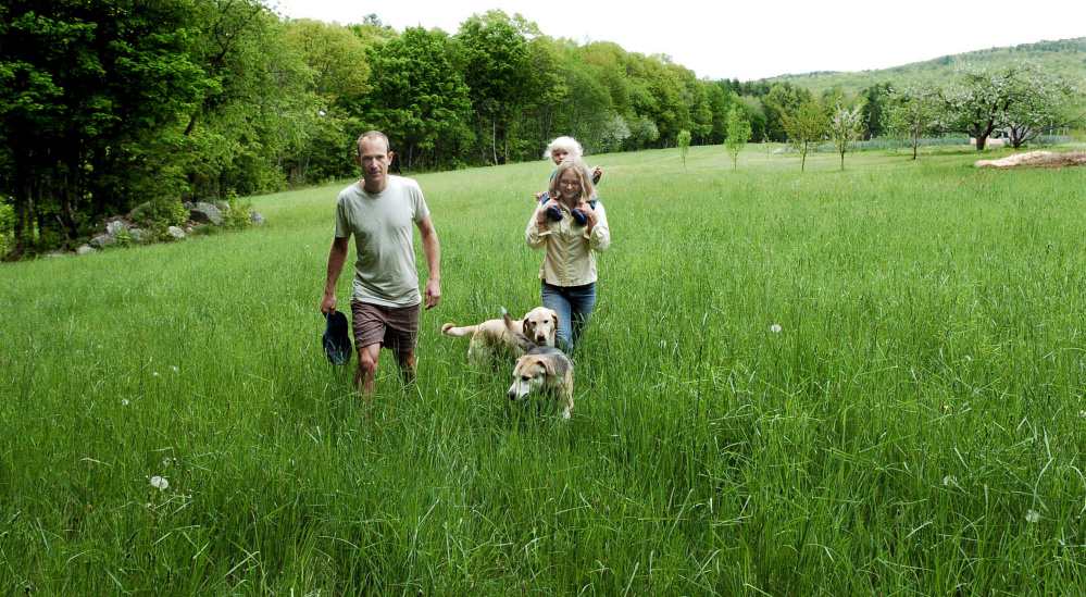 Marc and Lyra Collard, daughter Ara and dogs walk in a field in Norridgework, where they are establishing the Winding Hill Trails. The couple are opening the free public-access walking and running trails on their property with help from a New Balance Move More Kids grant.