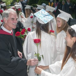 "Head of School Pat ""Mr. Mac"" McInerney hands out roses Saturday to female members of the class of 2016 in front of Bearce Hall before the graduation ceremony at Kents Hill School in Readfield."