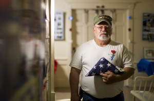 Army veteran Dennis Andrews of Boothbay Center displays a flag that flew over the White House during an event Saturday in the Southport Town Hall. Author Sarah Sherman McGrail worked with Sen. Susan Collins to honor Andrews.