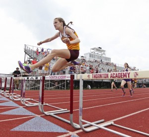 Allie Gross of Thornton Academy clears the final hurdle to win her heat in the 300-meter hurdles at the SMAA track and field championships in Saco.
