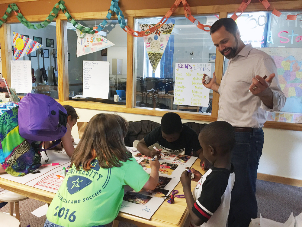 Volunteer mentor Jeremy Law of Cape Elizabeth works with children in the Exploration Station science and technology learning program at the Boys & Girls Club in Portland. Kelley Bouchard/Staff Writer