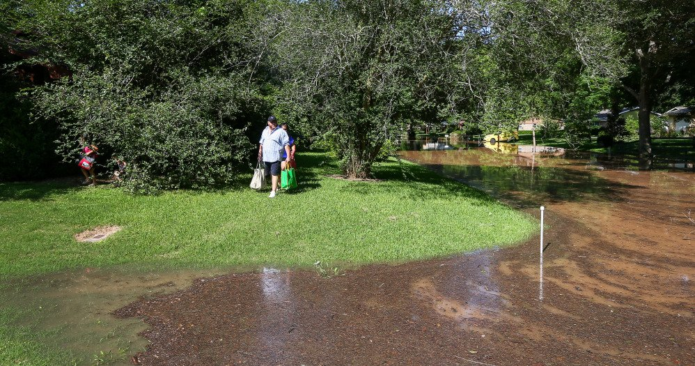 Jesus Lozano Jr. checks the rising water level as he and his family leave their home Sunday in Richmond, Texas, near the Brazos River, which is expected to rise another several feet.