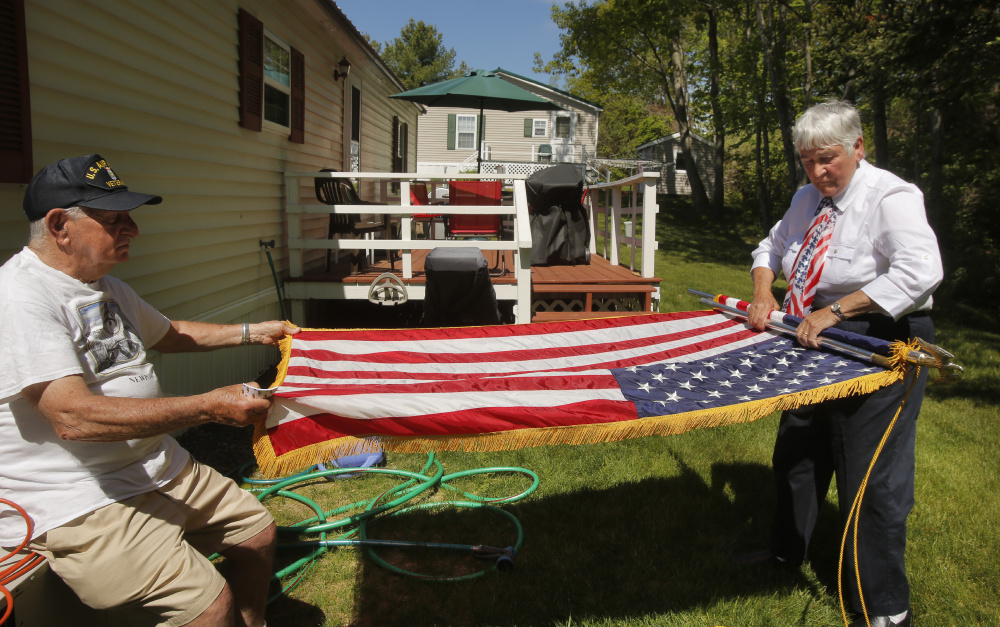 Lou Alexander helps his wife, Marion, fold a flag behind their home in Scarborough. Lou served 22 years in the Air Force doing aircraft maintenance, much of it during the Vietnam War, and the couple's son served 20 years in the same branch.