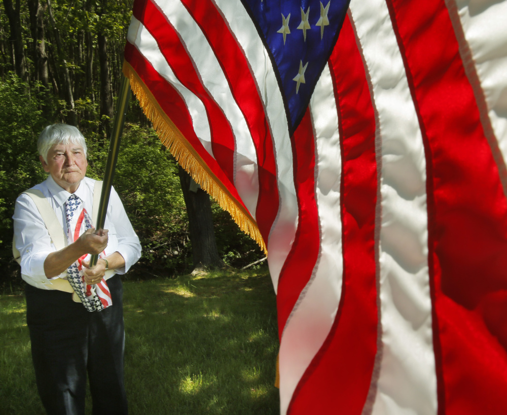 """Marion Alexander of Scarborough has been carrying the flag in Portland parades since 1982. """"I'll do it as long as I can,"""" she said."""
