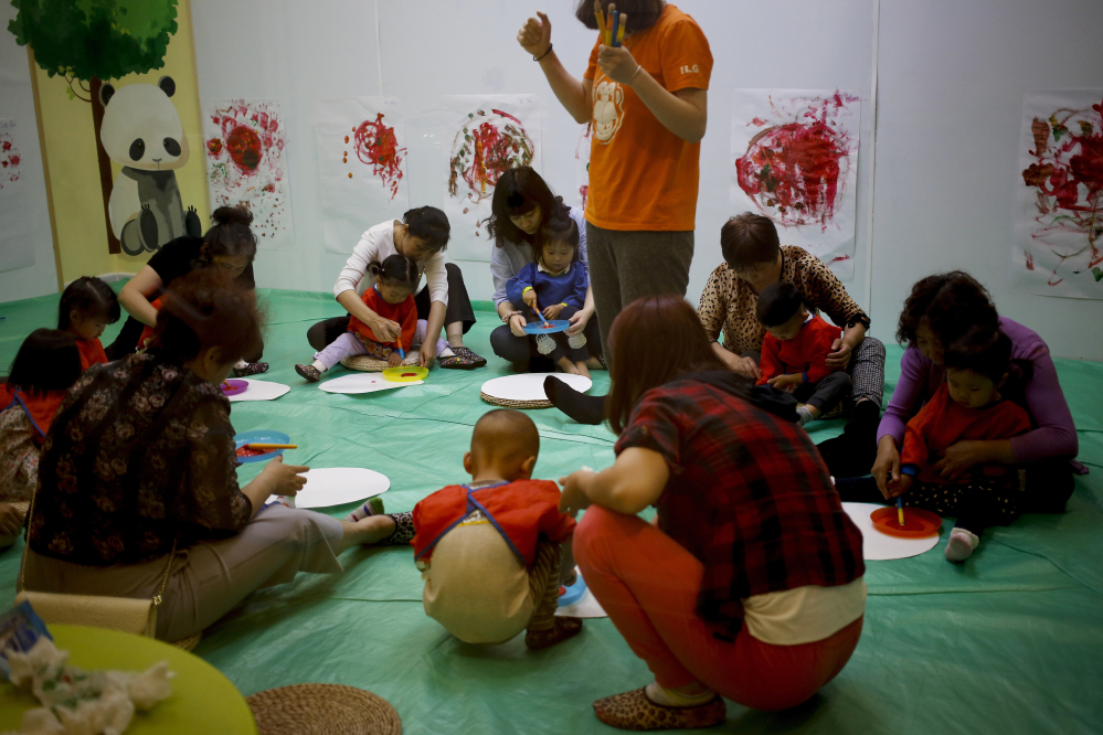 Children and their parents and caretakers attend an art class at the I Love Gym center in Beijing, China, earlier this month. The rise in use of in vitro fertilization points to the deferred dreams of many Chinese parents who had long wanted a second child.