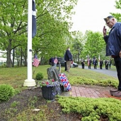 Phil Ceaser, commander of American Legion Post 76 in Scarborough, salutes after laying a memorial wreath at Black Point Cemetery during Memorial Day services in Scarborough on Monday.