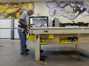 """Darryl Chase of STARC Systems works on a wall module at TechPlace, an emerging business at Brunswick Landing. Co-founder Bruce Bickford says the company is on pace to triple production and """"TechPlace has been a great place to be."""" The wall art remains from the former naval air base."""