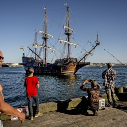 Motor power propels the Spanish tall ship El Galeon into Portland Harbor on Tuesday as fishermen take in the spectacle at the end of the Maine State Pier. After a Coast Guard inspection Wednesday, the ship is expected to be open for public tours at its berth on the Maine Wharf.
