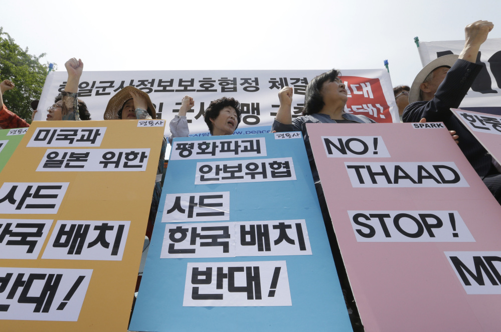 South Korean protesters stage a rally denouncing the United States, South Korean and Japanese governments' missile policies on North Korea in Seoul, South Korea, Tuesday.