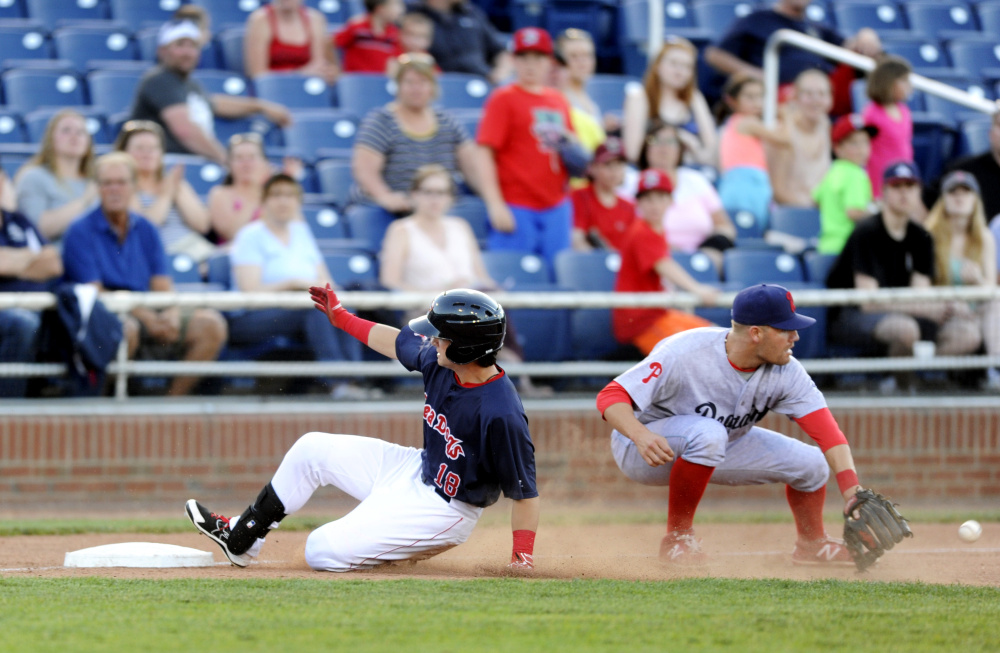 Andrew Benintendi of the Portland Sea Dogs slides into third base, reaching on a single and moving around when the ball was misplayed in the outfield. Two runs scored on the fifth-inning play at Hadlock Field. Derek Davis/Staff Photographer