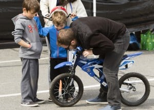 Jackson Kayne, 7 and his brother, Nolan, 5 of Portland, watch as their father, Kevin, adjusts Nolan's new bike bought at 16th annual Bike Swap at USM in Portland on Sunday. Sponsored by the Bicycle Coalition of Maine, over one thousand bikes were available for sale, by individuals and dealers, and over 2,000 people were expected to attend, according to Bicycle Coalition of Maine Communications Director Brian Allenby. Proceeds of sales, an estimated $125,000  go back into the pockets of sellers, with a 15% commission going to support the mission of the coalition to make the riding and walking experience better in the state.