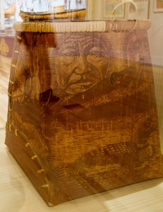 The shadow of a visitor is reflected in a glass case containing pack baskets from different Wabanaki tribes.