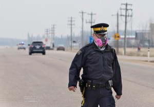 A police officer wears a mask while controlling a roadblock near a wildfire in Fort McMurray, Alberta, Canada on Thursday. Raging wildfires in the Canadian province of Alberta moved south, forcing three more communities to evacuate and an emergency operations center to move again.