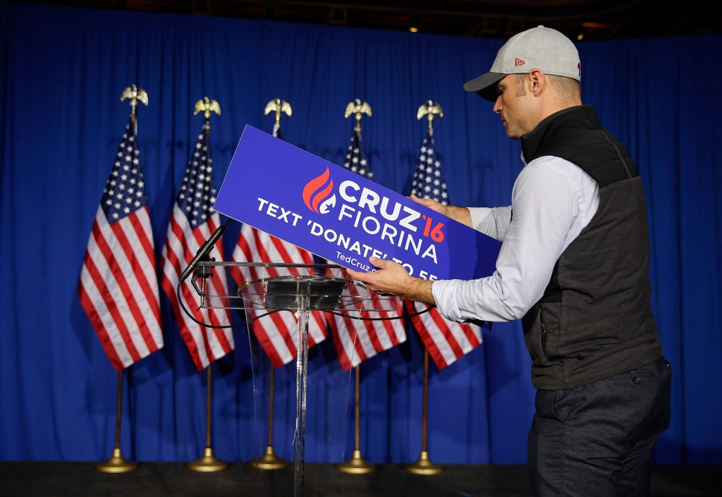 A worker for Ted Cruz removes the campaign sign from the podium after Cruz's speech in Indianapolis in which he announced the end of his presidential campaign. The Associated Press